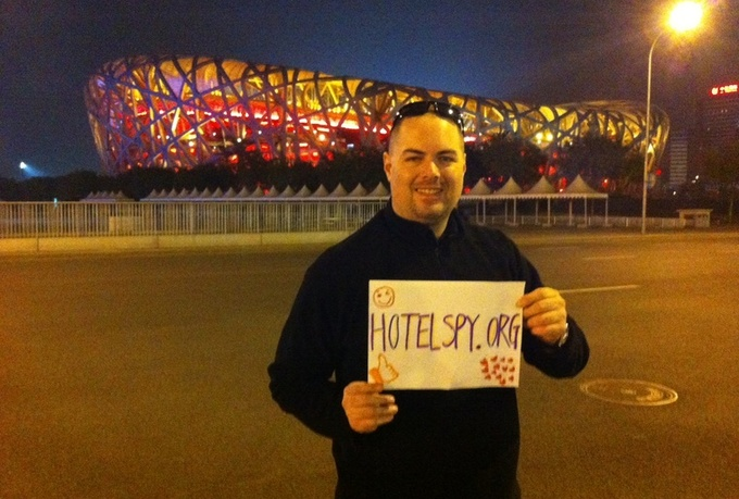 take a photo holding a handwritten sign for you standing in front of the Beijing Olympic Birds Nest Stadium